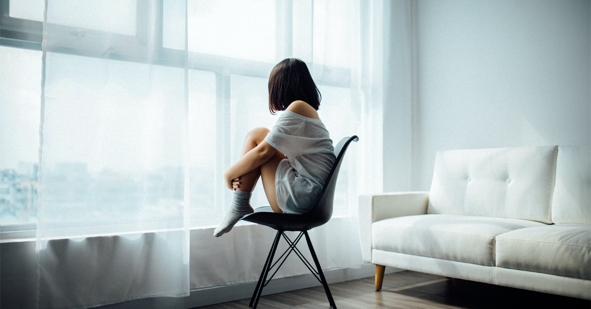 a woman sat on her own in her living room suffering from lockdown loneliness, looking out of the window