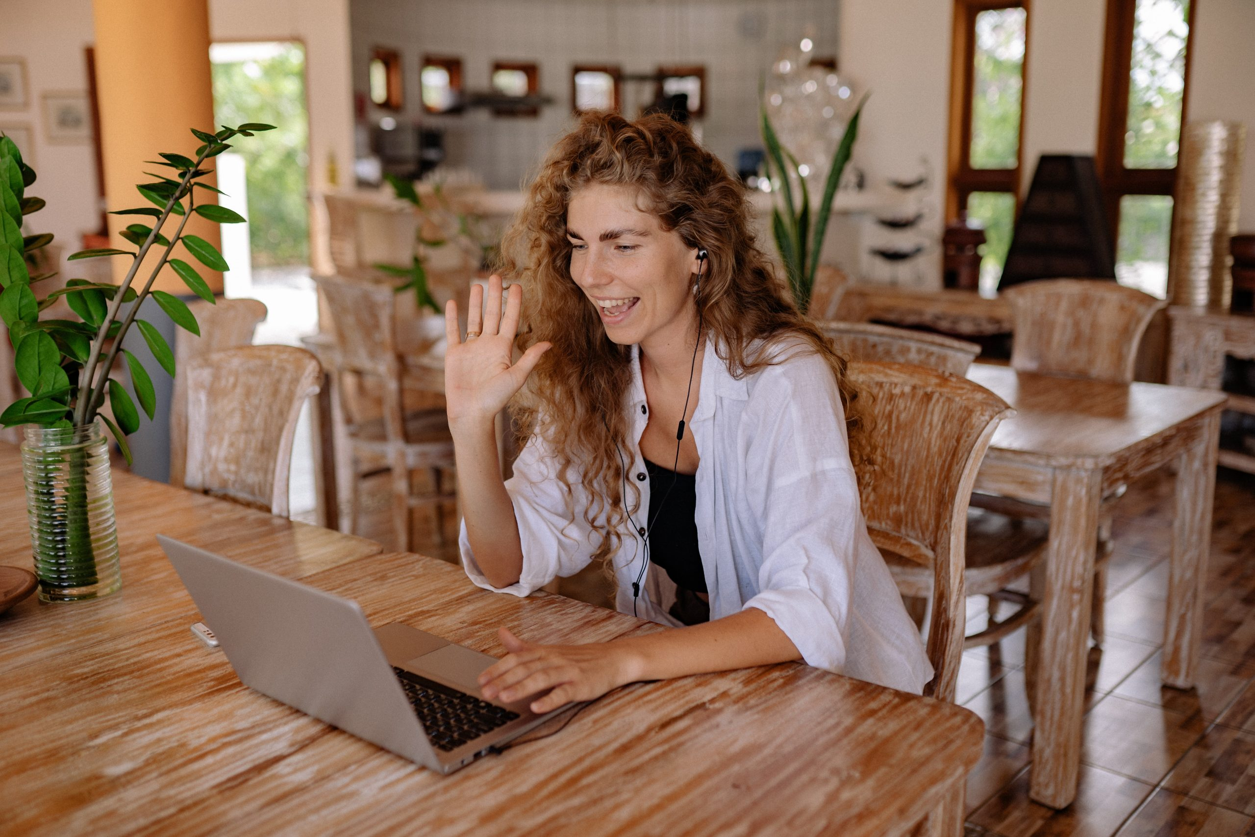 a woman sitting at a table with her laptop video-calling someone